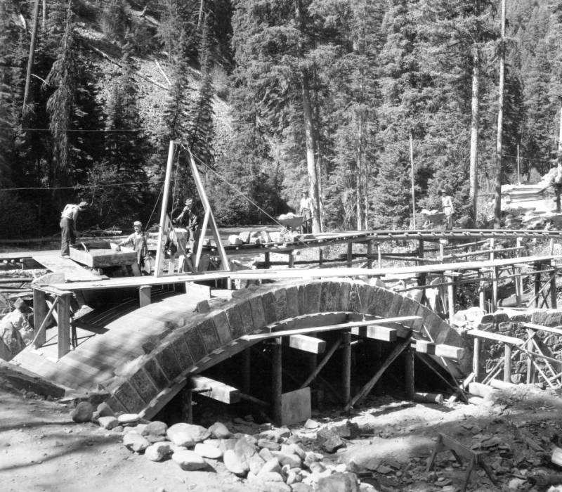 Stone arch bridge at Deep Creek under construction by CCC labor, Deep Creek, Bitterroot National Forest, Idaho<br />Stone arch bridge at Deep Creek under construction by CCC labor, Deep Creek, Bitterroot National Forest, Idaho, Swan, K. D., 1938-08-01