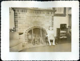 Young Bill Hopkins poses for a Christmas photo in front of a fireplace