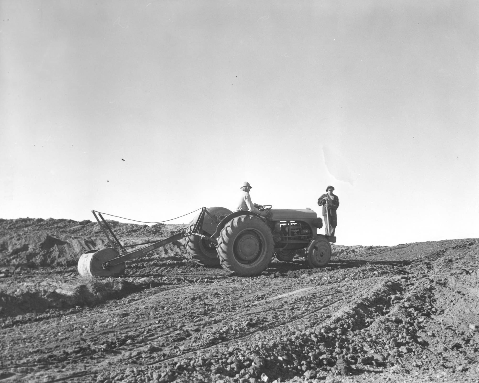 item thumbnail for Two CCC workers level land with tractor