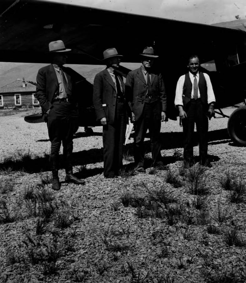 item thumbnail for Men associated with national forests pose in front of plane