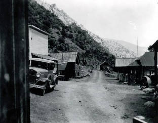 item thumbnail for Bayhorse, Idaho showing dirt road with several buildings and old cars.