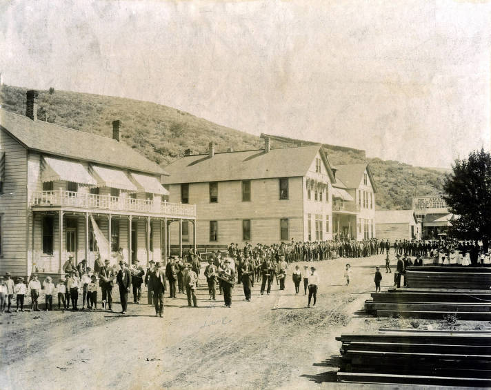 item thumbnail for Crowd of people in street with band in foreground. DeLamar Mercantile in background. DeLamar, Idaho.