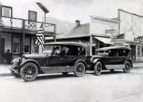 item thumbnail for View of two cars parked on street. Buildings partially shown are Midway and a bakery. Orofino, Idaho.