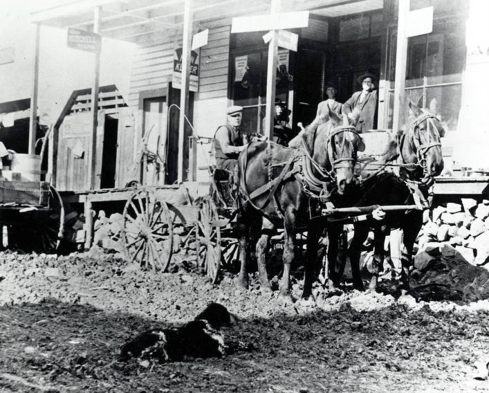 item thumbnail for Wagon pulled by team and men on porch in front of Erb Brothers General Store.
