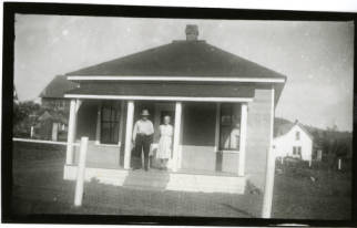 Image of Melton couple in front of home