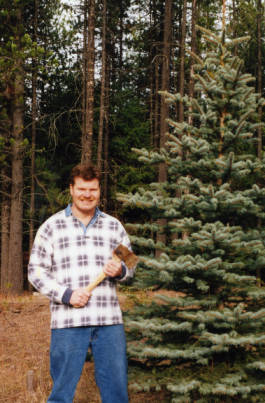 Image of Johann Miner (son-in-law of Wilma Daniels) in front of tree with axe