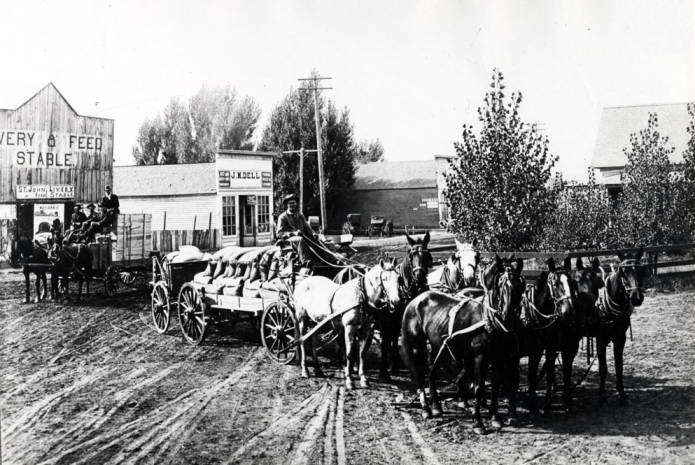 item thumbnail for Eight horses pulling two wagons of grain