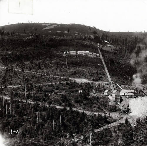 Mace (Idaho), Northern Pacific engine - Explosion, 1907<br/ >Close-up view of the Northern Pacific train engine explosion debris.  Various citizens can be seen examining the wreckage, which has come close to some of the houses.