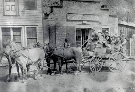 Image of Buggy full of men and women pulled by four horses. Challis, Idaho.