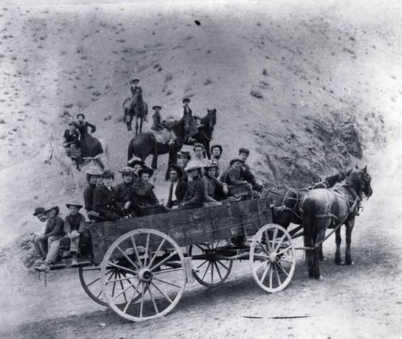 Image of Wagon load of people and several on horses. Challis, Idaho area.